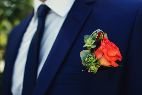 Red rose flower fresh boutonniere on stylish dark blue suit clos