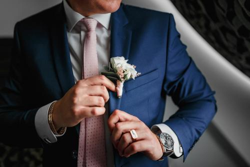 wedding details - elegant groom dressed in fashion costume with luxury boutonniere is waiting for the bride
