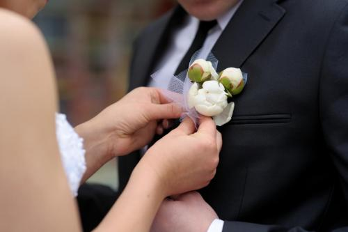 Bride adjusting groom's boutonniere